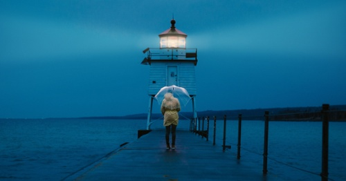 Person with Umbrella in Front of Lighthouse