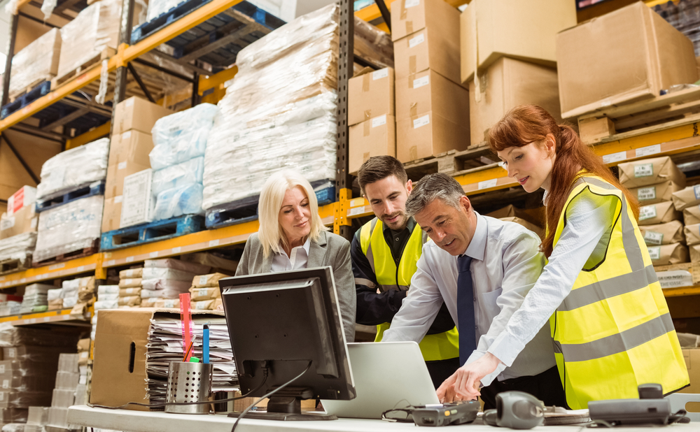 Warehouse managers and worker talking in a large warehouse